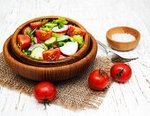 foto of radish  - Spring salad with tomato cucumbers and radish on a wooden background - JPG