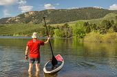 stock photo of horsetooth reservoir  - male paddler is about to step on his SUP paddleboard  - JPG