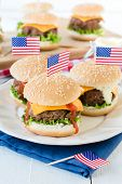 stock photo of beef-burger  - American mini beef burgers with cheese and USA flags in plateselective focus - JPG