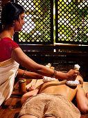 stock photo of panchakarma  - Woman having Ayurveda massage with herbal ball - JPG