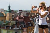 foto of observed  - Young attractive girl photographs on smartphone Old European Town from top the observation tower - JPG