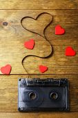 pic of heart sounds  - Audio cassette with magnetic tape in shape of heart on wooden background - JPG