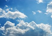 Bright white and dark stormy cumulus clouds with a blue sky in the middle