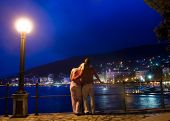 Couple standing near the sea and looking at night city panorama
