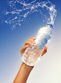 stock photo of bottle water  - Human hand holding a bottle of water - JPG