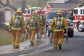 stock photo of retarded  - fire fighters carrying their tools and equipment head to a house on fire.