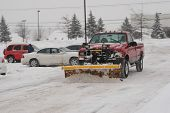 picture of parking lot  - snow plow clearing a parking lot after snow storm - JPG