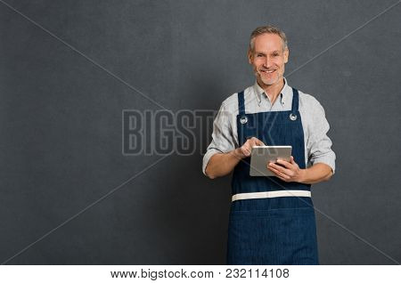 poster of Smiling man using digital tablet for his business isolated on grey background. Portrait of happy mat