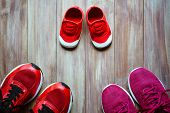 Three Red Sport Running Shoes Or Sneakers Of Mother And Father And Child On Wooden Background,use Fo poster