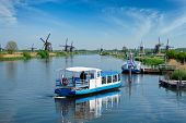 Netherlands rural lanscape with tourist boat and windmills at famous tourist site Kinderdijk in Holl poster