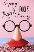 a pair of fake eyeglasses, with nose and mouth, and the text happy april fools day, on a rustic surf poster