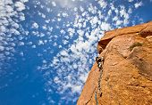 rock climbing:young climber on a steep granitic mountain over a blue sky