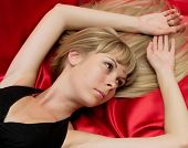 Portrait girl lying on a red background