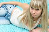 young blonde girl in jeans and white shirt