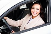 Happy owner of a new car. Smiling young pretty woman sitting in her automobile poster