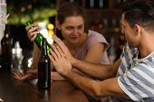 Young man refusing to drink beer in bar. Alcoholism problem