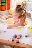 Little cute girl painting at table indoors