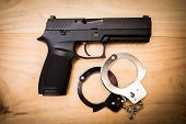 Hand Gun With Hand Cuffs On Wooden Surface poster