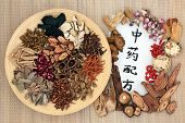 Chinese alternative medicine with herbs on a wooden plate on bamboo background with calligraphy scri poster