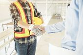 Success Deal In Construction And Interior Job. Businessman And Engineer Handshaking At Site. Picture poster