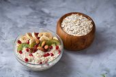 Diet Breakfast Oatmeal Cereal With Kiwi, Banana, Almond And Pomergranate Seeds And Wooden Bowl With  poster
