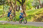 Happy Family Is Riding Bikes Outdoors And Smiling. Mom On A Bike And Son On A Balancebike. poster