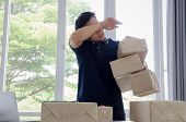 Tired Handsome Young Asian Delivery Man Wiping Sweat And Lifting Many Packaging Parcel Box In Home O poster