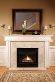 stock photo of mantle  - An upscale home with burning fireplace gives the feeling of being warm - JPG