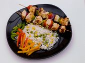 Grilled Chicken On A Black Plate With Rice.