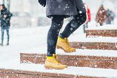 A Young Woman In Yellow Leather Boots Rises On Icy Snowy Granite Steps In Urban Environment. Winter  poster