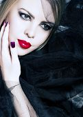 beautiful woman with red lips, smoky eyeshadow and purple manicure on the background of black veil w