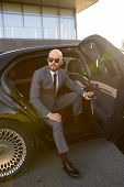 A Bald Business Man With Beard In An Expensive Suit In An Expensive Car poster