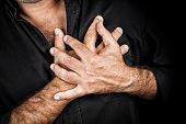 Close up of two hands grabbing a chest on a black background, useful to represent a heart attack or