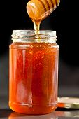 Honey sticky trickle dropping in a jar against a black background