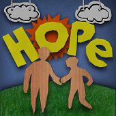 A paper and cardboard cutout diorama with the word Hope in front of the sun with clouds in the sky and two people - and adult and child - holding hands on grass