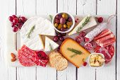 Serving Platter Of Assorted Meats, Cheeses And Appetizers. Top View On A White Wood Background. poster