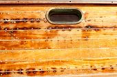 boat oval aged brass porthole in wooden hull with caulking putty and screw