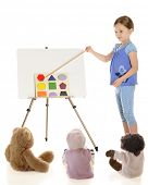 A young elementary girl teaching her toys about shapes.  On a white background.