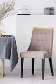 Stylish Chair Next To Dining Table With Grey Tablecloth In Trendy Dining Room Interior poster