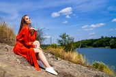 Portrait Of A Beautiful Young Woman In Red Long Dress. Lake View. Nature Background. Long Hair. Nice poster
