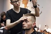 Young Barber Kazakh Works In A Barbershop, Handsome Guy Does Hair Styling For A Client With Dry Gel poster