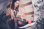 Beautiful Woman Reading Book At Home In Swing Chair. Woman Relaxing In Swing Chair At Home. Hipster  poster