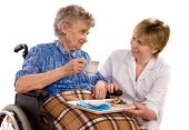 stock photo of crippled  - Health care worker and elderly woman in wheelchair needs help - JPG