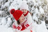Mother And Child In Knitted Winter Hats In Snow. poster