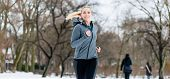 Woman running or jogging down a path on winter day in park poster