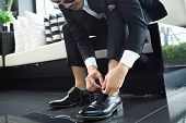 Business Man In A Black Suit Tie A Black Leather Shoe On Black Floor. The Hands Of A Business Man Wh poster