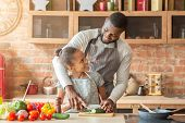 Cheerful African Father Teaching Daughter Cutting Veggies, Cooking Together At Home, Father And Daug poster