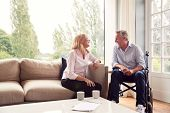 Mature Couple With Man In Wheelchair Sitting In Lounge At Home Talking Together poster