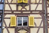 Colorful Facade Of Old Half-timbered House With Multiple Windows And Wooden Shutters, Close-up. Medi poster