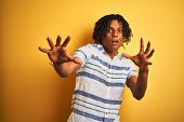 Afro american man with dreadlocks wearing striped shirt over isolated yellow background afraid and t poster